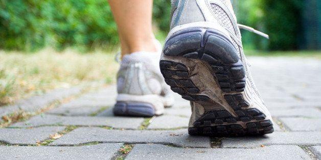 woman walking on sidewalk ...