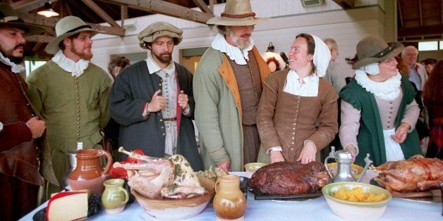 PLYMOUTH, MA - SEPTEMBER 19: Costumed interpreters gather around  a table loaded with food for the Harvest Feast of 1621, or 'The First Thanksgiving,' at Plimoth Plantation in Plymouth, Mass. (Photo by Pam Berry/The Boston Globe via Getty Images)