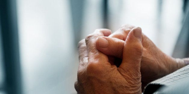 old woman's hands clasped...