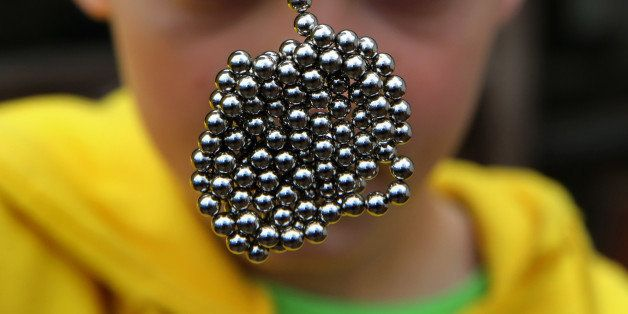 Brandon Bruski, 9, holds dozens of Buckyballs on Thursday, April 11, 2013 in Crystal Lake, Illinois.  In January, Brandon accidentally swallowed two balls from this set of the small magnetic desk toys.  The magnets left Brandon with a small and large intestine bound together.  Emergency surgery was required. (Chris Sweda/Chicago Tribune/MCT via Getty Images)