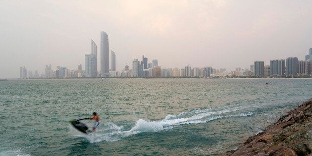 Skyscrapers stand on the city skyline beyond a jet skier passing close to the shore in Abu Dhabi, United Arab Emirates, on Mo
