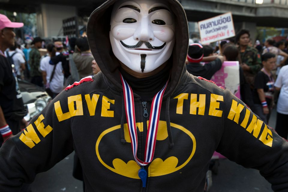 "An anti-government protestor displays his hoodie that reads ""We love the King"" outside MBK Center shopping mall in the Pathum"