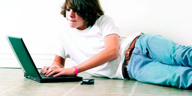 Teenage boy laying on floor working on laptop computer with cell by his side . (Photo by: Universal Education/Universal Images Group via Getty Images)