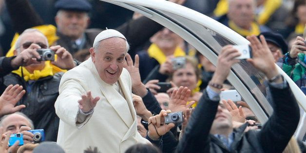 Pope Francis greets the crowd as he arrives for his general audience at St Peter's square on January 22, 2014 at the Vatican.  AFP PHOTO / ANDREAS SOLARO        (Photo credit should read ANDREAS SOLARO/AFP/Getty Images)