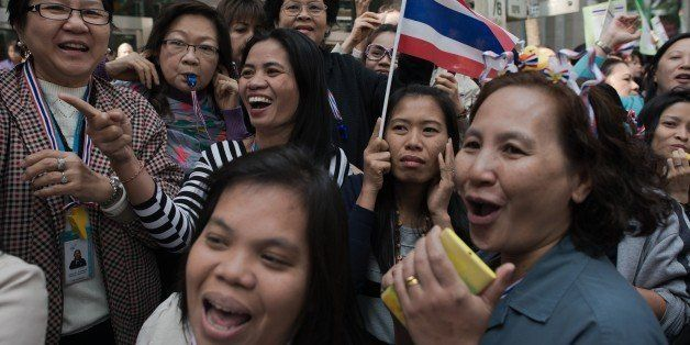 Thai anti-government protesters watch Thai protest leader Suthep Thaugsuban (not seen) as he marches in the streets during ongoing rallies in Bangkok on January 23, 2014. Defiant Thai opposition protesters vowed to ignore a state of emergency that came into force across the tense capital on January 22, refusing to abandon their fight to bring down the government. AFP PHOTO/ Nicolas ASFOURI        (Photo credit should read NICOLAS ASFOURI/AFP/Getty Images)