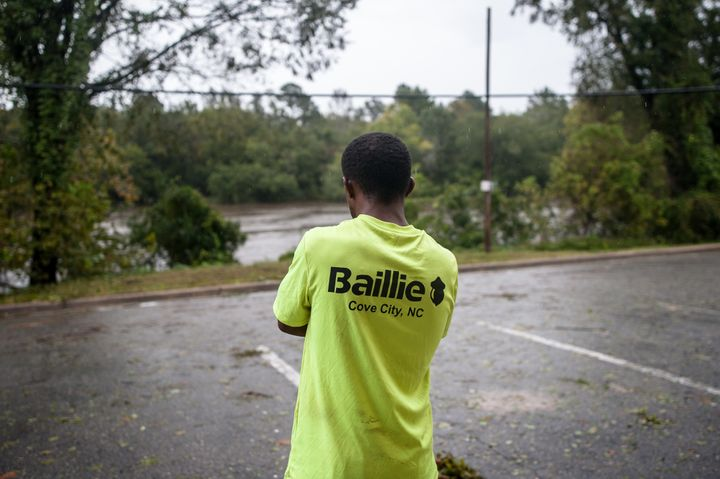 Junior Lor, after evacuating from New Bern, North Carolina, looks out from his hotel in Kinston at the rising Neuse River on