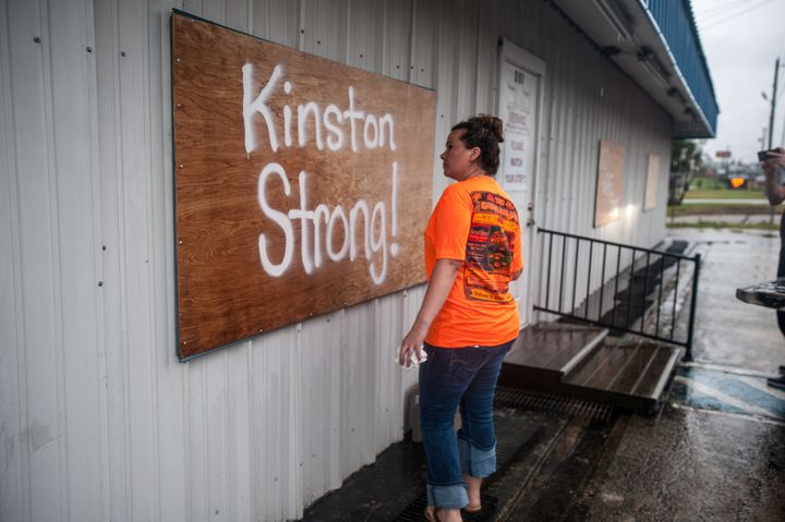 """Rhoda Rikard paints """"Kinston Strong!"""" on a board covering the window of her family business, Southland Flooring and Design, a"""