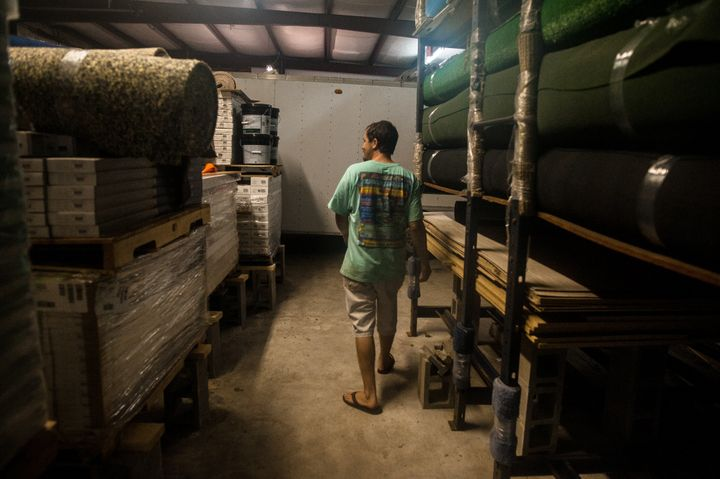 Kendall Rickard walks through the warehouse of Southland Flooring and Design, where he and Rhoda placed all products on cinde