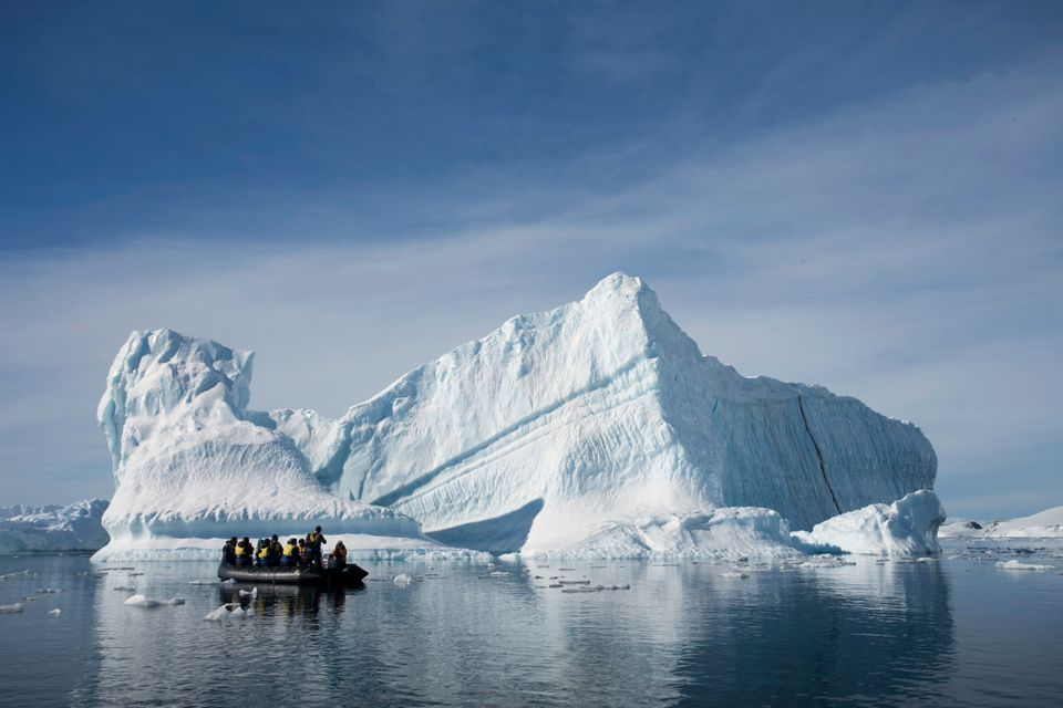 In this Dec. 1, 2009 photo provided by Aurora Expeditions, an inflatable boat carries tourists past an iceberg along the Anta
