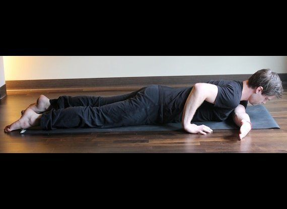 Lay down on your belly.  Place your right hand in a pushup position near the base of your ribs.  Lift your chest slightly, an