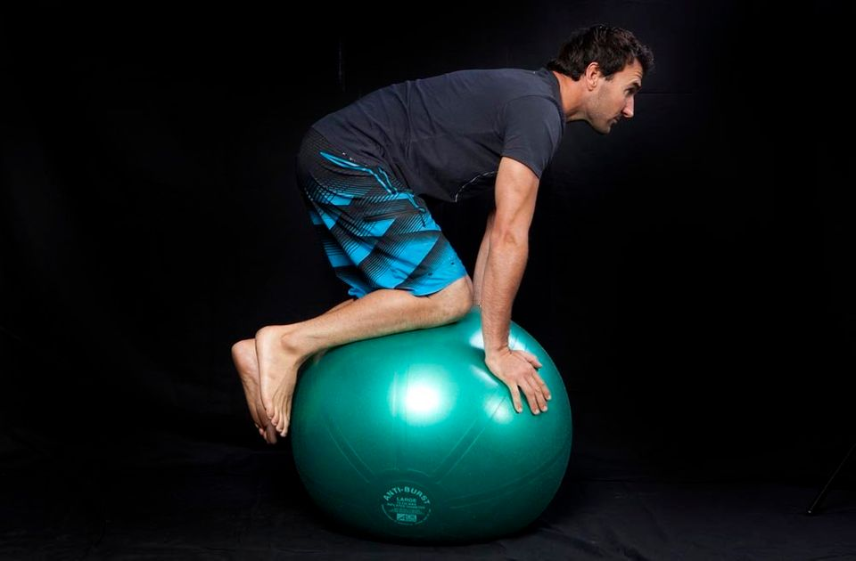 Kneel on the ball using your hands for balance. Keep your back flat and engage your core.