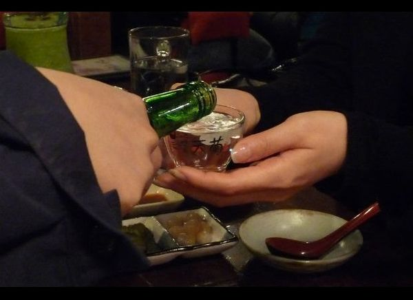 When picking up, pouring, and drinking an alcoholic drink in Japan and Korea, they use both hands because it's bad manners to