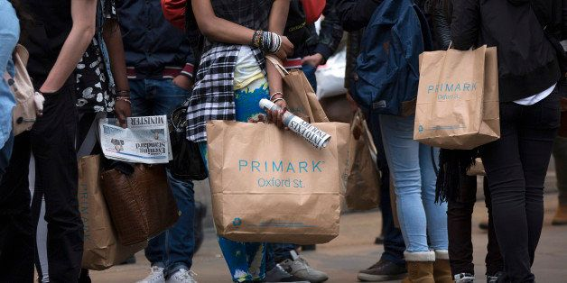 Pedestrians hold Primark branded shopping bags as they wait to cross a road on Oxford Street in London, U.K., on Thursday, Ap