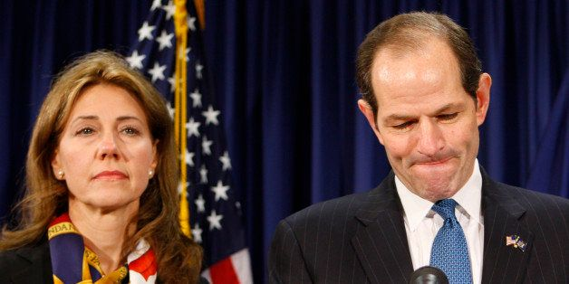 UNITED STATES - MARCH 12:  Eliot Spitzer, New York governor, flanked by his wife Silda Wall Spitzer, left, addresses the media in New York, U.S., on Wednesday, March 12, 2008. Spitzer announced that he will resign next week as governor of New York, brought down by allegations that he patronized a ring of high-priced prostitutes.  (Photo by Andrew Harrer/Bloomberg via Getty Images)