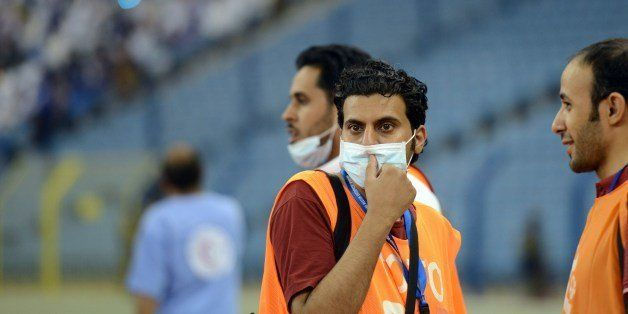 Saudi photographers wear mouth and nose masks during a football match at the King Fahad stadium, on April 22, 2014 in Riyadh.