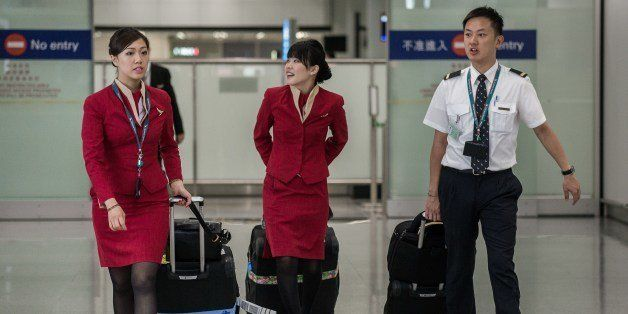 Flight attendants (L and C) for Cathay Pacific are seen arriving at the international airport in Hong Kong on May 5, 2014.  Cathay Pacific flight attendants want the Hong Kong airline to redesign their uniforms because they are too revealing and may provoke sexual harassment, a union said on May 5. AFP PHOTO / Philippe Lopez        (Photo credit should read PHILIPPE LOPEZ/AFP/Getty Images)