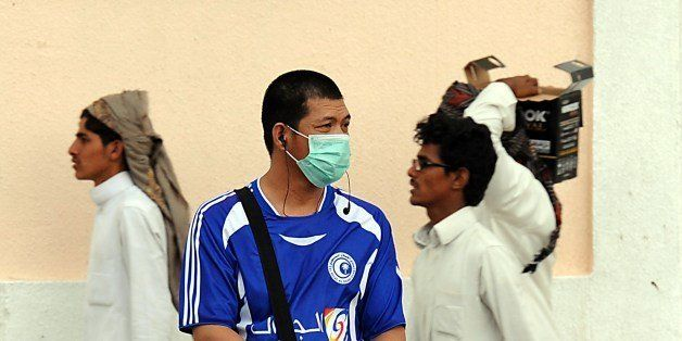 A foreign worker living in Riyadh wears a mask covering his mouth and nose on a main street in the Saudi capital on April 29, 2014 as the death toll from the newly emerged and often fatal Middle East Respiratory Syndrome (MERS) disease topped 100 in the desert kingdom. The health ministry reported more MERS cases in the city of Jeddah, prompting authorities to close the emergency department at the city's King Fahd Hospital. AFP PHOTO/FAYEZ NURELDINE        (Photo credit should read FAYEZ NURELDINE/AFP/Getty Images)