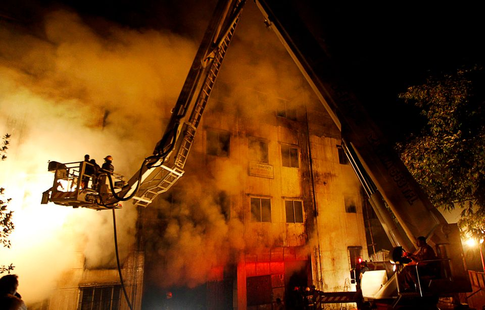 Bangladeshi firefighters battle a fire at a garment factory in the Savar neighborhood in Dhaka, Bangladesh, late Saturday, No
