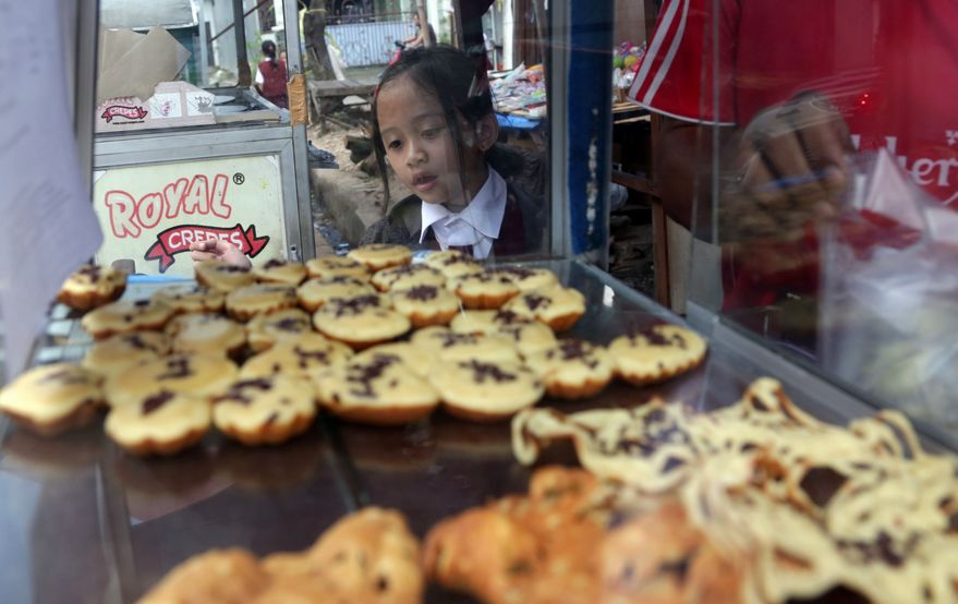 A public elementary school girl buys a pancake for her lunch on the street in Jakarta, Indonesia, Tuesday, May 6, 2014. In In