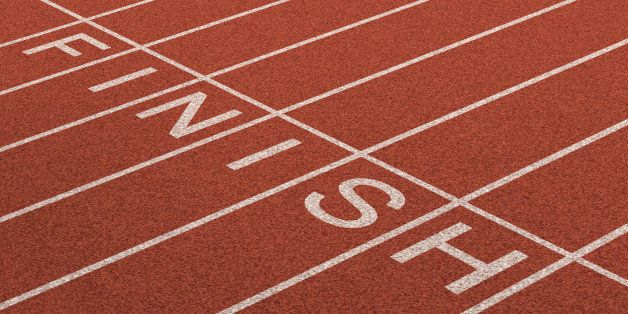 Finish Line as a business symbol of success in completing a planned strategy to achieve victory and reach the goals of financial freedom and wealth as a track and field background in perspective.
