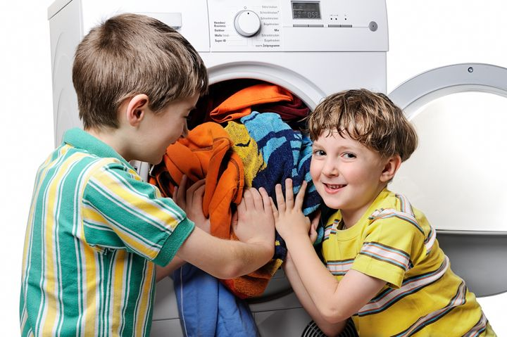 funny boys loading clothes to...