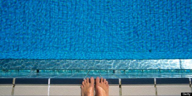 Feet at edge of swimming pool, elevated view