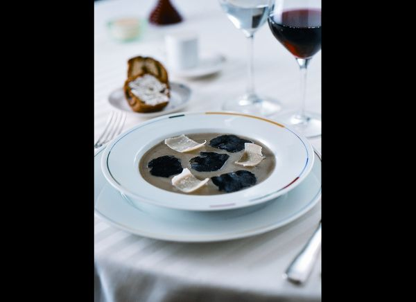 Guy Savoy's signature artichoke and black truffle soup, served with a layered brioche with mushrooms and truffles