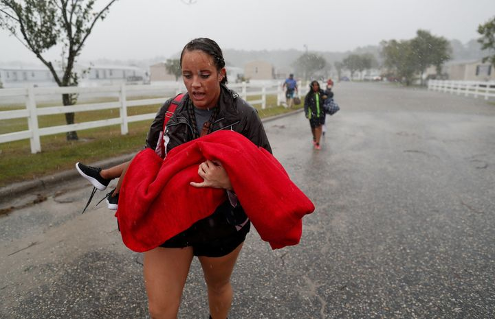 Maggie Belgie of The Cajun Navy carries a child as a flooding trailer community is evacuated during Hurricane Florence in Lum