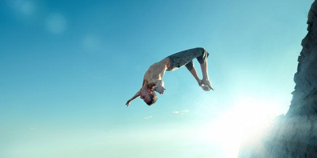 Portrait of an excited young man jumping in air against blue sky