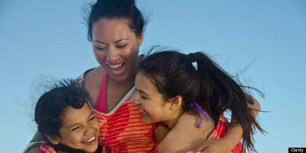 Mom having fun with her two daughters on the beach