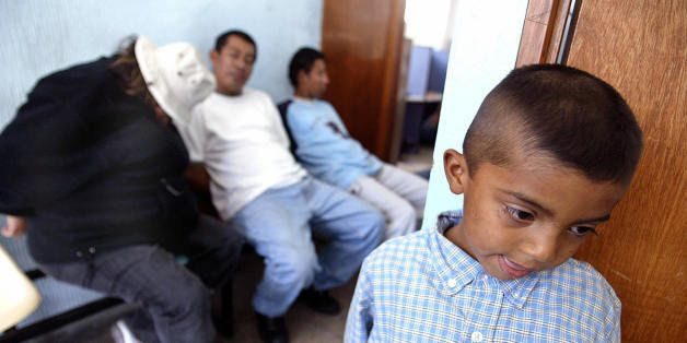 SAN SALVADOR, EL SALVADOR:  Marvin Cristino Ventura(R) who is 7 years old, waits in a Police Border Station near of US citizen Heather Livengood Mc Clung (L) and  Salvadoreans Humberto Ibarra (C) and Juan Moran (R) on February 10, 2004. The three last ones were arrested accused of people traffic when they were carrying five Salvadorean children to their families in the United States.   AFP PHOTO/ Yuri CORTEZ  (Photo credit should read YURI CORTEZ/AFP/Getty Images)