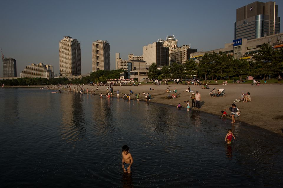 People enjoy the beach at the Odaiba shoreline on May 31, 2014 in Tokyo, Japan. Odaiba is a large artificial island on Tokyo