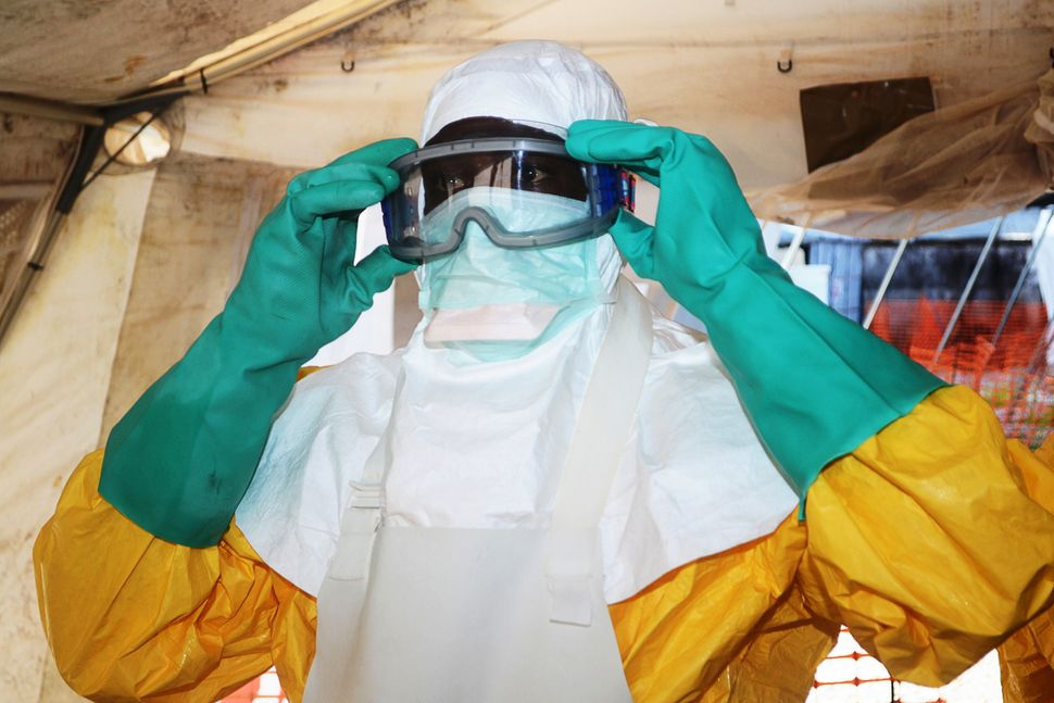A member of Doctors Without Borders puts on protective gear at the isolation ward of the Donka Hospital in Conakry, where peo