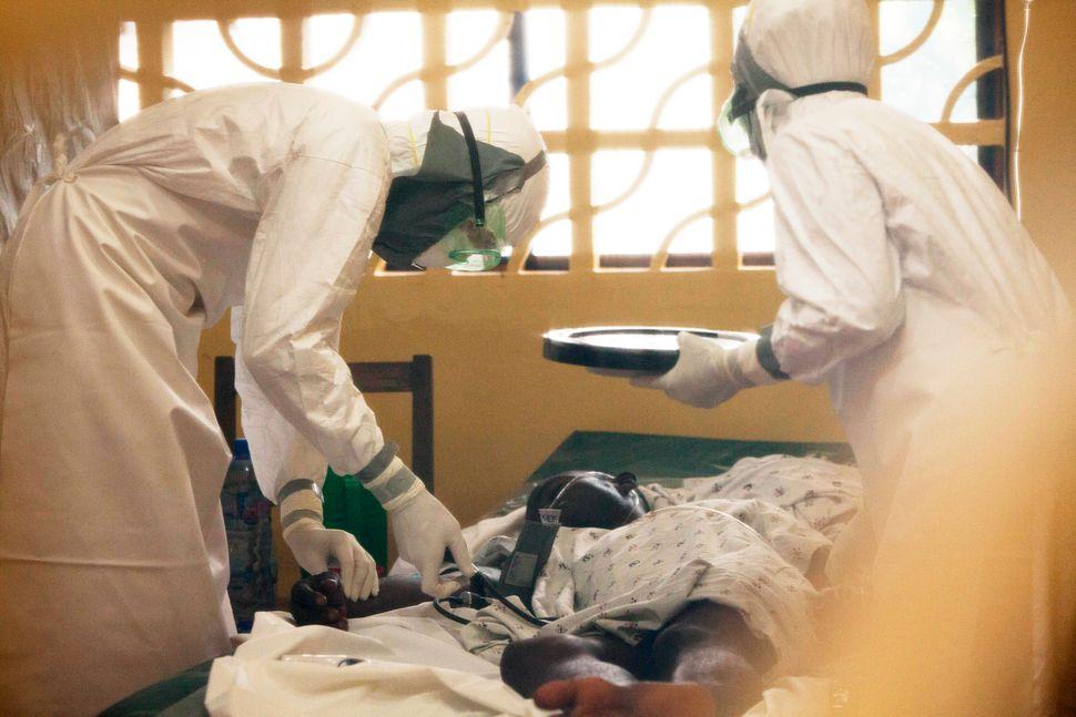 Dr. Kent Brantly, left, treats an Ebola patient at the Samaritan's Purse Ebola Case Management Center in Monrovia, Liberia. O