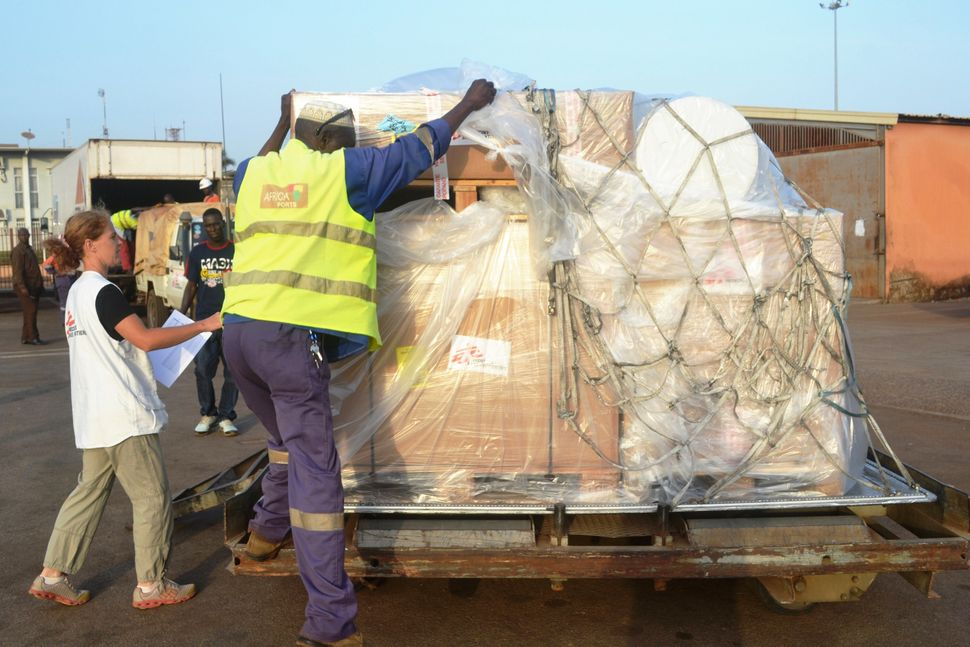 A worker loads material including protection gear for Doctors Without Borders at the airport of Conakry on March 29, 2014. (C