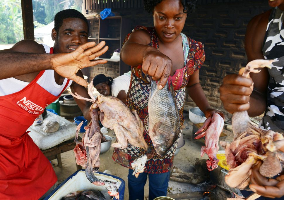 """The owners of a """"maquis,"""" a small African restaurant in Kobakro, outside Abidjan, which used to serve bush meat, hold up the"""