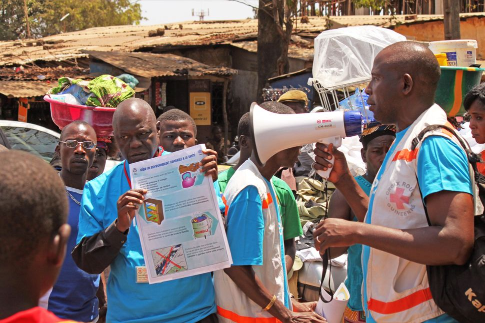 Health workers teach people about the Ebola virus and how to prevent infection, in Conakry, Guinea, on March 31, 2014. (Youss