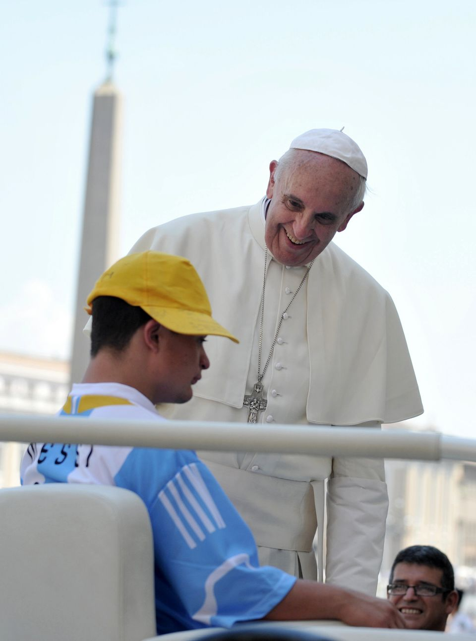 Pope Francis talks with a young boy on his popemobile at the end weekly general audience in St Peter's square at the Vatican