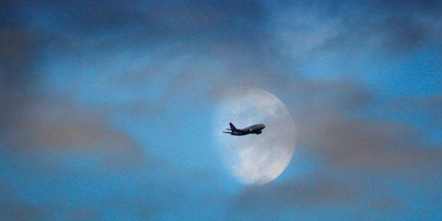 A Lufthansa passenger jet passes the moon on approach to landing at Heathrow Airport. PRESS ASSOCIATION Photo. Issue date: Sa