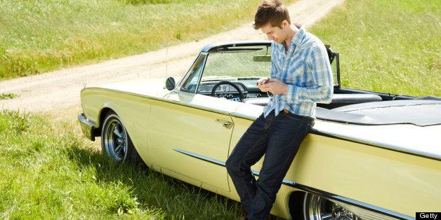 Side view of a young man using a smart phone sending a text message. He is standing by vintage car during summer road trip. H