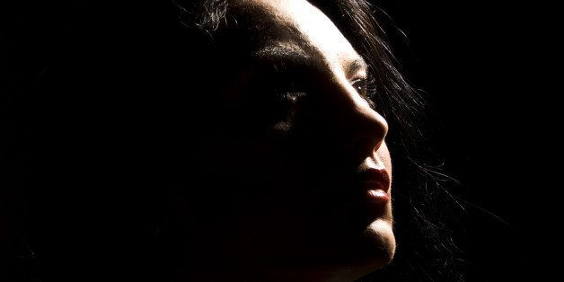 Portrait of beautiful brunette woman looking away in darkness  with soft light on her face