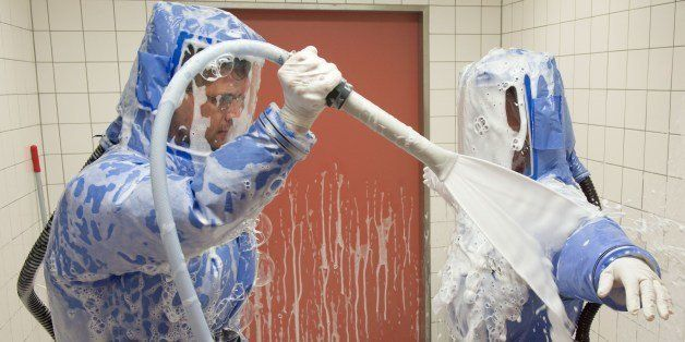 Infectious disease specialist Florian Steiner (L) and quarantine office leader Thomas Klotzkowski disinfect themselves during
