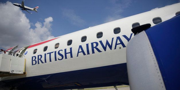 A British Airways jet, operated by IAG SA, climbs after take-off beyond a parked airliner at London City Airport Ltd. in London, U.K., on Wednesday, Aug. 6, 2014. London City Airport, where a short runway has prevented operations with long-haul planes, said it's in talks about flights to the Middle East, Turkey and Russia as new jets bring more distant destinations within reach. Photographer: Matthew Lloyd/Bloomberg via Getty Images