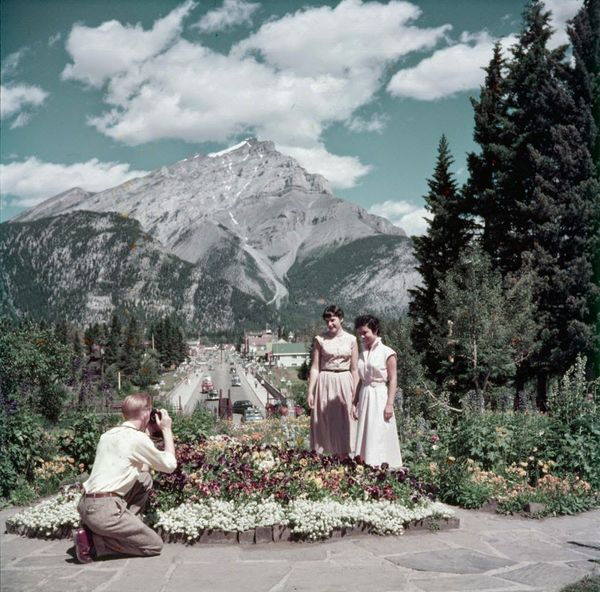 "Man takes photograph of two women in front of administration building in Banff.  <a href=""http://collectionscanada.gc.ca/pam_"