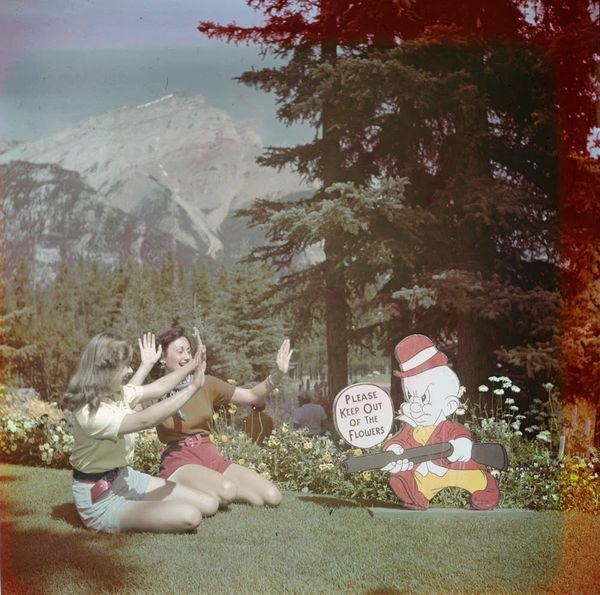 "Two women posing with a cartoon sign on the lawn of the Administration Gardens, Banff National Park.  <a href=""http://collect"