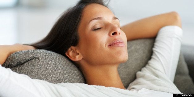 Pretty woman on sofa smiling with eyes closed