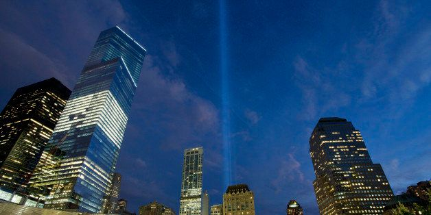 In this Monday, Sept. 8, 2014 photo, the Tribute in Light rises behind buildings adjacent to the World Trade Center in New York. The art installation consists of 88 searchlights aiming skyward in two columns, in memory of the former twin towers. Four World Trade Center is at left. Thirteen years after 9/11 forever changed the New York skyline, officials say developments at the World Trade Center are on track and on budget. (AP Photo/Mark Lennihan)