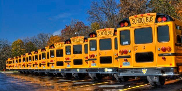 This is an HDR photo of a  line of parked school buses at Millburn school in Millburn Illinois