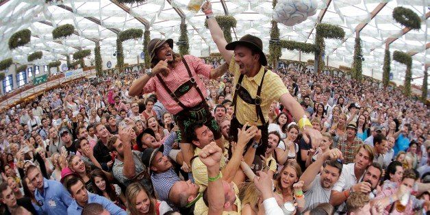 In this photo taken with a fisheye lens, people celebrate the opening of the 181th Oktoberfest beer festival in Munich, southern Germany, Saturday, Sept. 20, 2014. The world's largest beer festival will be held from Sept. 20 to Oct. 5, 2014. (AP Photo/Matthias Schrader)