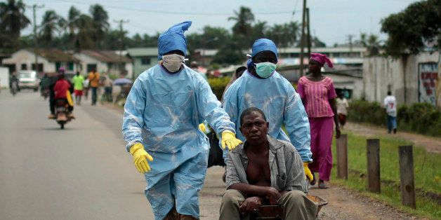 Residents of the St. Paul Bridge neighborhood wearing personal protective equipment take a man suspected of carrying the Ebola virus to the Island Clinic in Monrovia, Liberia, Sunday Sept. 28, 2014. Six months into the worldᅢ까タᅡルs worst-ever Ebola outbreak, and the first to happen in an unprepared West Africa, the gap between what has been sent by other countries and private groups and what is desperately needed is huge. Even as countries try to marshal more resources to close the gap, those needs threaten to become much greater, and possibly even insurmountable. (AP Photo/Jerome Delay)